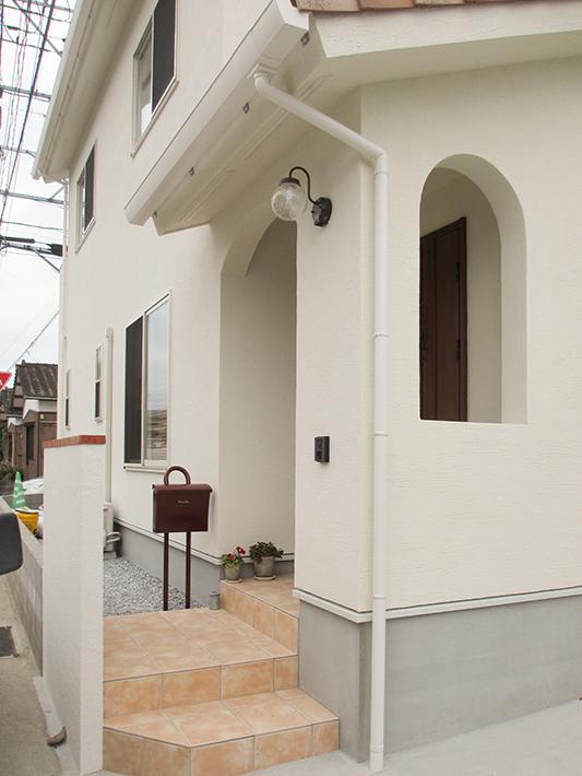 塗り壁を生かしたアーチ型の下がり壁やくり抜きのあるかわいいエントランス。