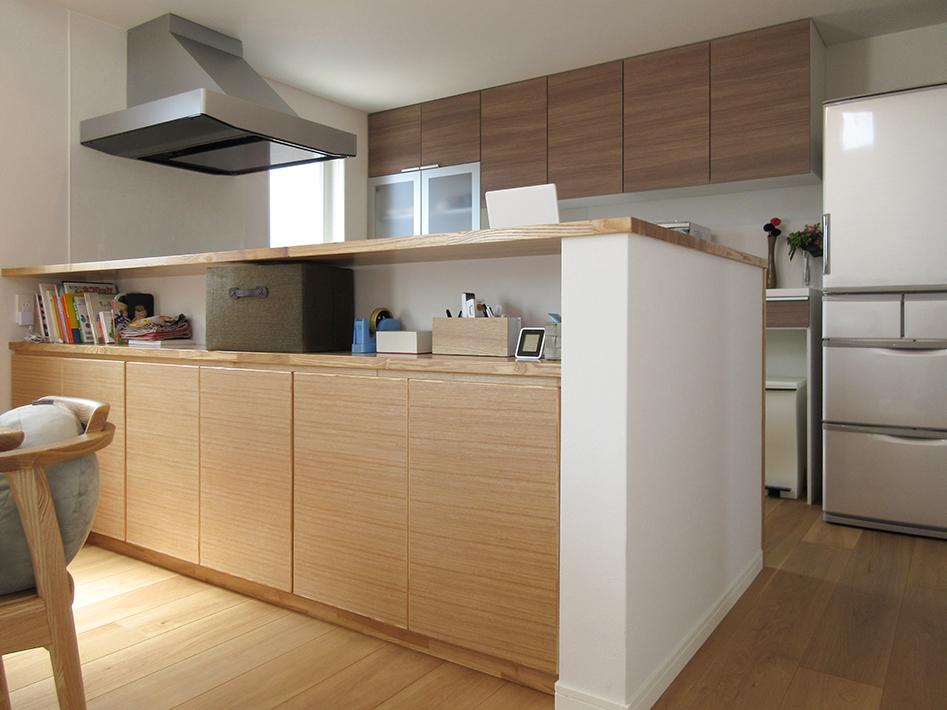 対面キッチンのカウンターは、見せる収納と隠す収納を分けた造作家具の組み合わせ。