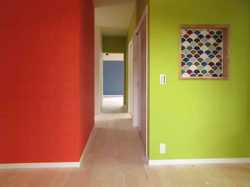 玄関ホールから廊下にかけて、深みのあるビビッドカラーで貼り分けました。