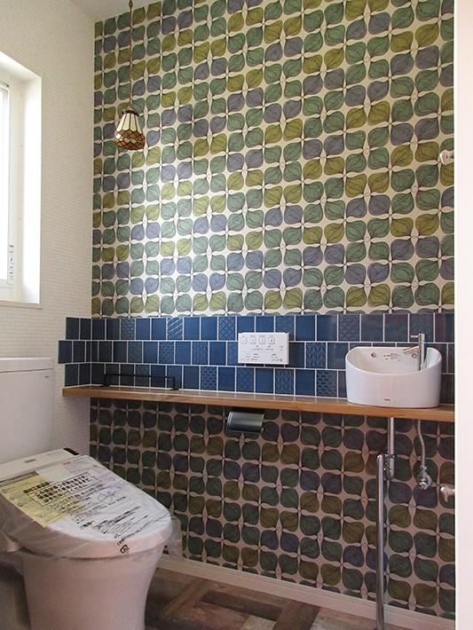 トイレには古典柄をモダンにアレンジしたタイルと木の葉模様のクロスを使用。