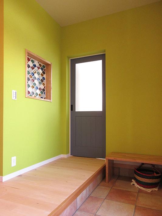 玄関横の個室入口は、淡いブルーに塗装した木製ドア。