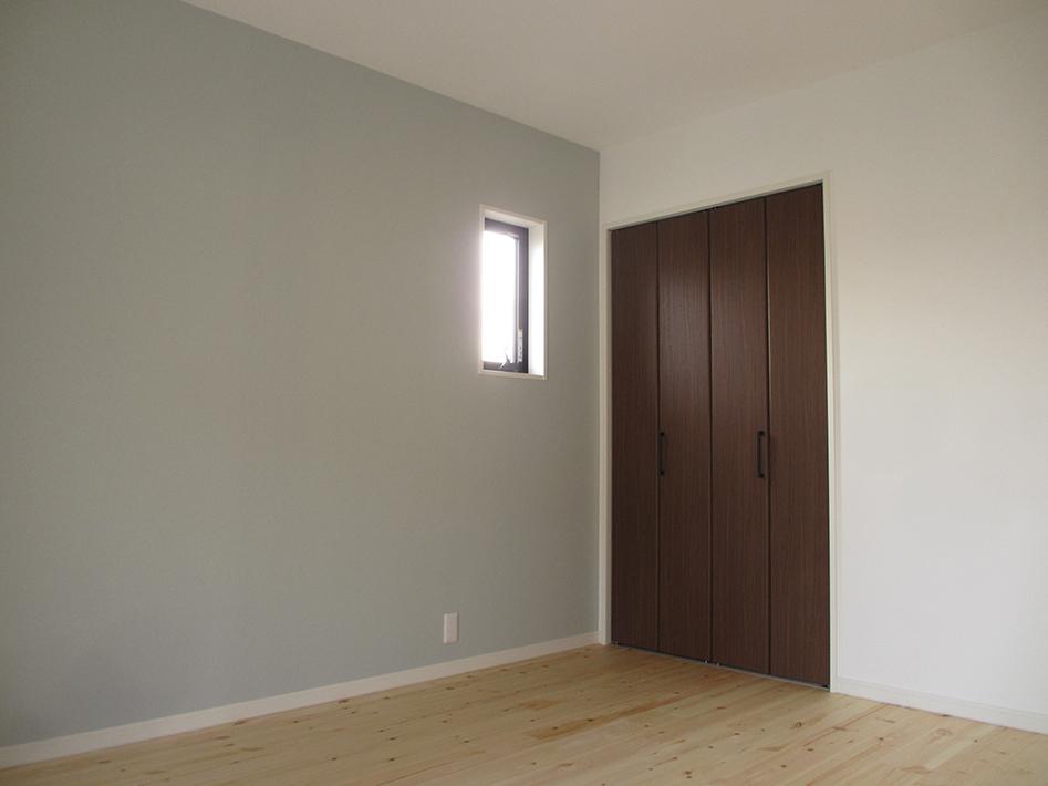グレイッシュな壁紙とダークブラウンの建具がクールな配色の洋室。