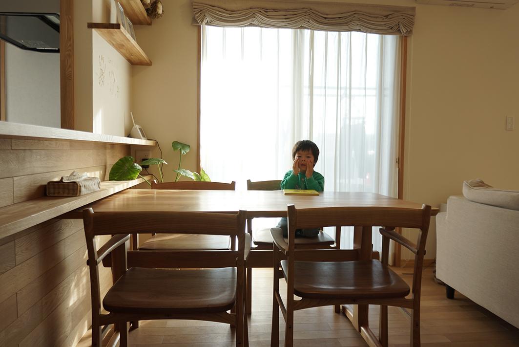 ダイニングテーブルはオーダーの品。キッチンカウンターの棚板の下に入るようにぴったり。